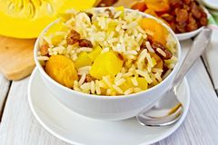 Pilaf fruit with pumpkin in bowl and spoon Royalty Free Stock Image