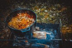 Pilaf im großen Kessel auf dem Feuer lizenzfreies stockfoto