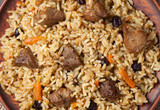 Pilaf with large pieces of fried meat, spicy rice. Carrot and raisins. Traditional arabian gourmet. Close-up macro shot Stock Photos