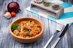 Pilaf with meat and carrots in wooden bowl. On rustic background Royalty Free Stock Photography