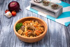 Pilaf with meat and carrots in wooden bowl. On rustic background Stock Photo