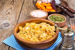 Pilaf with meat and carrots in wooden bowl on the table. Studio Photo Stock Images