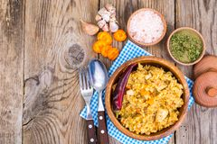 Pilaf with meat and carrots in wooden bowl on the table. Studio Photo Stock Image