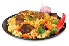 pilaf with meat and chili pepper on black plate isolated on white background stock photos