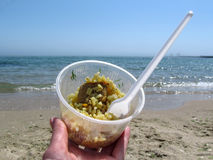 Pilaf with meat in a plastic container against the blue sea. A female hand holds rice in a disposable dish on the beach Stock Photos