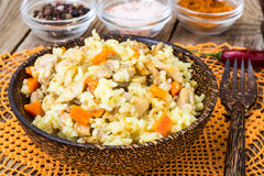 Pilaf with meat, rice and zira in a wooden bowl Royalty Free Stock Images