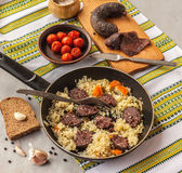 Pilaf in a pan and black pudding Royalty Free Stock Photo