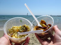 Pilaf, potato slices and sailboat on the horizon in the sea. Takeaway food to relax on the beach Stock Photo