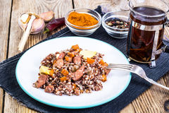 Pilaf with red rice with chunks of beef, carrots and garlic Royalty Free Stock Photo