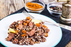 Pilaf with red rice with chunks of beef, carrots and garlic Stock Photo