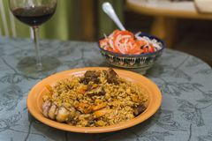 Pilaf with red wine in a glass and a salad of tomato and onion. Oriental dish of rice and meat royalty free stock images