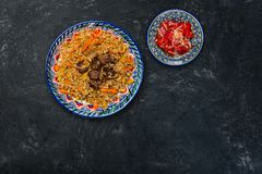 Pilaf and salad achichuk on plate with oriental ornament on a dark background. Central-Asian cuisine - Plov. Top view stock photography