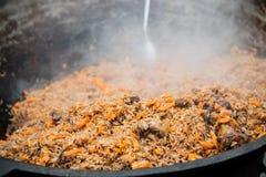 Pilaf savoureux d'Ouzbékistan dans un chaudron sur le feu en plein air au festival de nourriture de rue image libre de droits