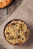 Pilaf is spicy indian food cooked with lot of rice. Fried meat, carrot, onion and garlic. Served in clay bowl with raisins, fresh backed bread and vegetables Royalty Free Stock Image