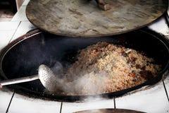 Pilaf tradicional caliente del Uzbek en una caldera con una tapa de madera Foto de archivo