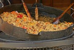 Pilaf y carne fritos en los pinchos en un sartén grande Imagenes de archivo