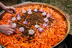 Pilaff - adding some garlic bulbs. Preparation of mutton pilaff - Uzbek national meal of mutton, rice, carrots, garlic and spices Royalty Free Stock Images