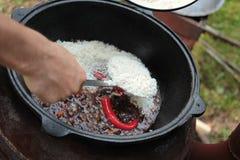 Pilaff förbereder sig i stort svart gjutjärn med kockar räcker royaltyfria foton