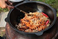 Pilaff förbereder sig i stort svart gjutjärn med kockar räcker royaltyfri foto