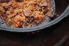 Pilaff förbereder sig i stort svart gjutjärn med kockar räcker arkivfoto