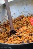 Pilaff i kittel En läcker pilaff med griskött, morötter och ris med kryddiga kryddor och lökar, i en kittel med en träspatel Royaltyfria Bilder