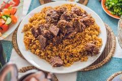 Pilaff med nötkött, morötter, lökar, vitlök, peppar och spiskummin En tr Arkivfoto
