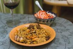 Pilaff med rött vin i ett exponeringsglas och en sallad av tomaten och löken Orientalisk maträtt av ris och kött royaltyfria bilder