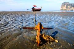 Pilar de acero con el barco del estacionamiento de la cuerda durante marea baja con la arena Foto de archivo libre de regalías