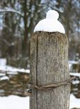 Pilar de madera con un casquillo de la nieve fotos de archivo