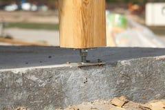 Pilar de madera en el hormigón del emplazamiento de la obra con el tornillo Los pilares de madera son las estructuras que se pued fotos de archivo