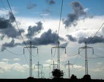 Pilares de la línea electricidad del poder en el cielo azul del fondo Foto de archivo