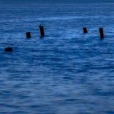 Pilares de madera quebrados en agua lisa en la oscuridad foto de archivo