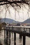 Pilares del embarcadero delante del paisaje de Como Fotos de archivo