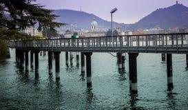 Pilares del embarcadero delante del paisaje de Como Foto de archivo libre de regalías