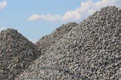 Pilas altas de la roca de la grava con el cielo azul brillante Imagen de archivo
