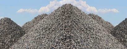 Pilas altas de la roca de la grava con el cielo azul brillante Imagenes de archivo