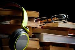 Pilas altas de libros con los vidrios y los auriculares del ojo fotografía de archivo libre de regalías