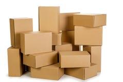 Pilas de cajas de cartón en un fondo blanco Imagen de archivo libre de regalías
