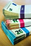 Pilas de cuentas euro en un escritorio del pino Imagen de archivo