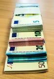 Pilas de cuentas euro en un escritorio del pino Fotos de archivo