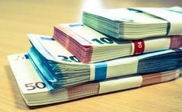 Pilas de cuentas euro en un escritorio del pino Imagenes de archivo