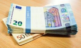 Pilas de cuentas euro en un escritorio del pino Fotografía de archivo libre de regalías