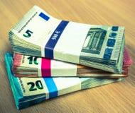 Pilas de cuentas euro en un escritorio del pino en fives, diez y años 20 Imagenes de archivo