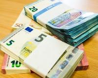 Pilas de cuentas euro envueltas en un escritorio del pino Imagenes de archivo