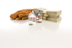 Pilas de dinero con los guantes del trabajo y la pequeña casa Foto de archivo libre de regalías