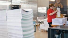 Pilas de edición impresa delante de la clase de la trabajadora los periódicos en la tipografía almacen de metraje de vídeo