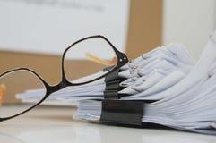 Pilas de ficheros de papel con los clips y los vidrios Foto de archivo