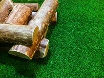 Pilas de la leña colocadas en hierba artificial foto de archivo