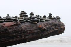 Pilas de la roca en un registro de la madera de deriva Fotos de archivo