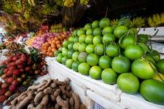 Pilas de las cales y de la otra fruta en mercado camboyano Imagen de archivo libre de regalías